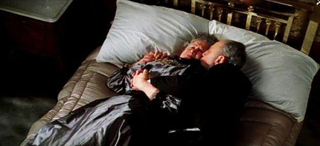 Пожилая пара, которая лежала, обнявшись на кровати
