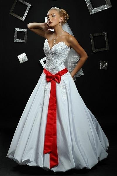Очень красиво смотрится свадебное платье с красной лентой, завязанной бантом. Бант может располагаться спереди