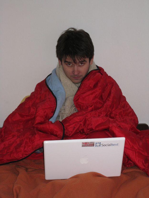 Мужчина с ноутбуком в одеяле