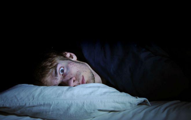 Мужчина на подушке с открытыми глазами
